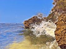 Vista della spiaggia con le rocce enormi e un'onda L'acqua di mare spruzza sopra le pietre Immagine Stock