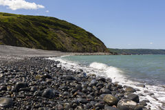 Vista della spiaggia di Greencliff ad alta marea, sembrante ovest del sud verso i mulini dei dollari, Devon, Regno Unito Fotografie Stock Libere da Diritti