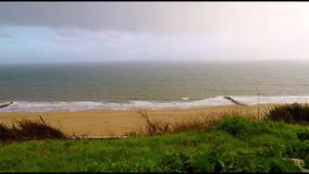 Vista della spiaggia sabbiosa con le colline un giorno piovoso, vegetazione verde, pioggia stock footage