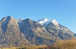 Vista della strada alle montagne svizzere e ad un castello nell'inverno Fotografie Stock