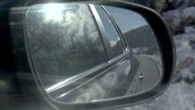 Vista della strada di inverno nel retrovisore di un'automobile Sun nelle nubi video d archivio