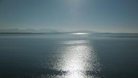 Vista della superficie di luccichio e luccicante del mare con le colline sull'orizzonte Incandescenza Defocused del sole che rifl stock footage