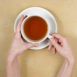 vista della tè-parte superiore delle mani femminili che tengono una tazza di tè Immagine Stock