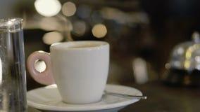Vista della tazza di caffè e del bicchiere d'acqua sulla tavola lentamente archivi video