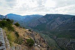 Vista della valle della montagna del calcare di Parnassus, degli oliveti verdi e di altri alberi con i pali luminosi del fondo e  fotografie stock