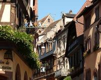 Vista della via di Riquewihr con le insegne Fotografie Stock