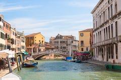 Vista della via di Venezia, delle case variopinte e del canale con le barche ed il ponte nel giorno soleggiato di Venezia, Italia immagine stock libera da diritti