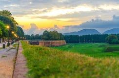 Vista della via pedonale del percorso di camminata con le luci delle lampade sul muro di cinta difensivo, sul campo verde dell'er fotografie stock libere da diritti
