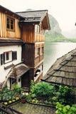 Vista della via sul lago alpino e sulle case di legno (Hallstat) Fotografia Stock