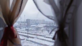 Vista della vicinanza in costruzione e delle file dei garage dalla finestra dell'appartamento nel grattacielo video d archivio