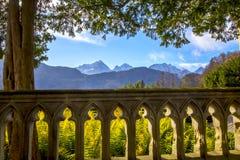 Vista delle alpi della montagna dal terrazzo con un bello recinto e le conifere Fotografia Stock Libera da Diritti