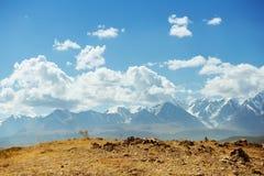 Vista delle alte montagne sui precedenti del cielo Fotografia Stock