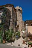 Vista delle case di pietra, della torre del castello e del vicolo stretto nel centro urbano storico di Gordes Immagini Stock
