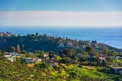 Vista delle colline verdi e delle case che trascurano l'oceano Pacifico Immagini Stock