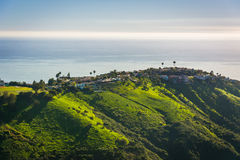 Vista delle colline verdi e delle case che trascurano l'oceano Pacifico Fotografia Stock