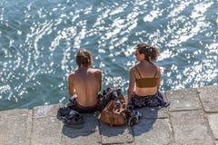 Vista delle coppie che si siedono sui bacini al fiume del Duero, prendenti il sole e godenti della vista fotografie stock libere da diritti