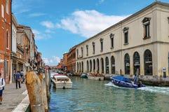 Vista delle costruzioni, davanti al canale, con la gente e le barche in Murano Immagine Stock Libera da Diritti