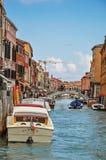 Vista delle costruzioni, davanti al canale, con la gente e le barche in Murano Fotografia Stock