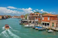 Vista delle costruzioni, davanti al canale, con la gente e le barche in Murano Fotografie Stock Libere da Diritti