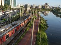 Vista delle costruzioni, del treno di CPTM, del traffico dei veicoli e del fiume nel viale marginale del fiume di Pinheiros immagine stock