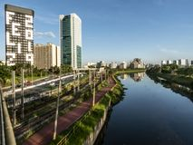 Vista delle costruzioni, del treno di CPTM, del traffico dei veicoli e del fiume nel viale marginale del fiume di Pinheiros fotografie stock libere da diritti