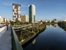 Vista delle costruzioni, del treno di CPTM, del traffico dei veicoli e del fiume nel viale marginale del fiume di Pinheiros fotografia stock libera da diritti