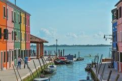 Vista delle costruzioni variopinte, della gente e delle barche davanti ad un canale a Burano Fotografie Stock Libere da Diritti
