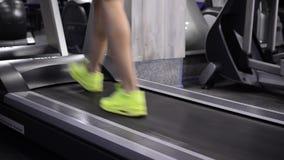 Vista delle gambe femminili che corrono sulla pedana mobile in palestra video d archivio