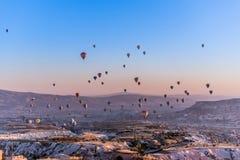Vista delle mongolfiere che volano da ogni parte di Cappadocia durante l'alba in fotografia stock libera da diritti