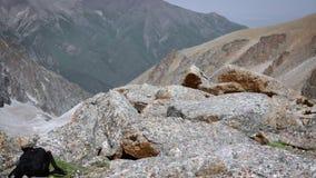 Vista delle montagne attraverso una grande pietra archivi video