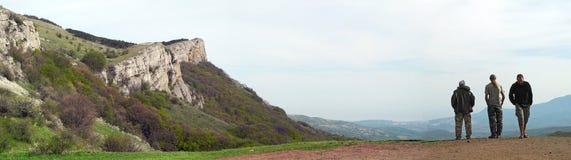 Vista delle montagne con tre uomini Due turisti, esaminare fotografie stock libere da diritti