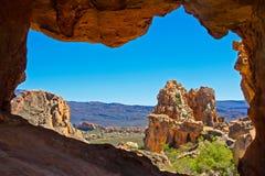 Vista delle montagne e delle rocce attraverso l'arco eroso dell'arenaria Fotografie Stock