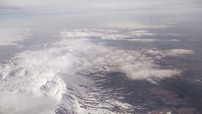 Vista delle nuvole e delle montagne innevate dall'oblò dell'aeroplano stock footage