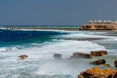 Vista delle onde selvagge che si rompono sopra il frangiflutti al pilastro a Calimera Habiba Beach Resort immagine stock