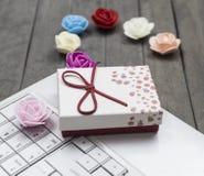 Vista delle rose, del computer portatile bianco e del contenitore di regalo rosso su fondo immagine stock libera da diritti