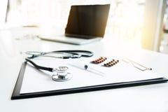 Vista dello stetoscopio, della droga e dell'attrezzatura sulla tavola della priorità alta con Fotografie Stock