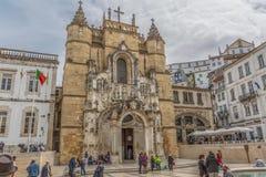 Vista dello stile romanico e gotico della facciata della parte anteriore di Santa Cruz Monastery, con i turisti sulla via, un mon immagini stock libere da diritti