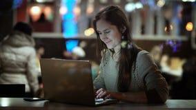 Vista dentro la finestra Giovane donna felice che si siede nella sera al caffè e che per mezzo del computer portatile, sorridente archivi video