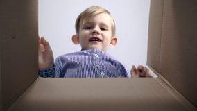 Vista desde adentro caja de cartón rubia del muchacho de la caja de cartón de la pequeña que es abierta metrajes