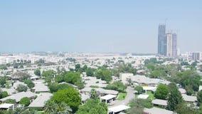 Vista desde arriba al Dubai con los rascacielos, las pequeñas casas, los caminos y los árboles existencias Antena para la ciudad  almacen de metraje de vídeo