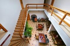 Vista desde arriba al pasillo del banquete con las sillas de tablas de las escaleras con las barandillas de madera que van abajo Foto de archivo libre de regalías