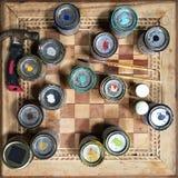 Vista desde arriba de las latas, de los cepillos y del martillo de la pintura en la tabla del tablero de ajedrez Foto de archivo libre de regalías