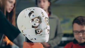 Vista detallada de la cara de un robot con los especialistas que hablan en el fondo almacen de video
