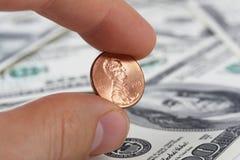 Vista detallada de la mano masculina que sostiene un penique en fondo con los billetes de dólar del americano ciento del dinero Imagen de archivo