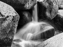 Vista detallada de la pequeña cascada del río en un río de la montaña rocosa Agua de seda borrosa por el tiro largo de la exposic foto de archivo
