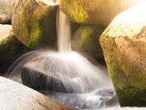 Vista detallada de la pequeña cascada del río en un río de la montaña rocosa Agua de seda borrosa por el tiro largo de la exposic imágenes de archivo libres de regalías