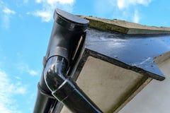 Vista dettagliata di uno scolo e di una grondaia recentemente dipinti veduti su una casa immagini stock libere da diritti