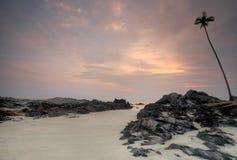 Vista di alba della spiaggia della sabbia con le rocce fotografia stock libera da diritti