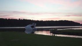 Vista di alba sopra il fiume Lielupe in primavera 2019 con una barca nella priorità alta - cielo vivo viola di rosa cremisi con i stock footage