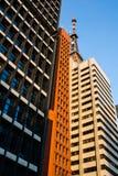 Vista di angolo basso delle costruzioni di affari con un'antenna della TV sulla cima Immagini Stock